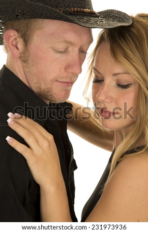 a cowboy with his woman looking down. - stock photo