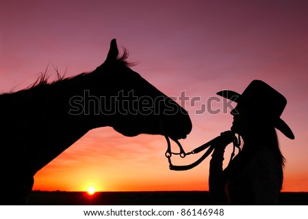 A cowgirl and her horse as the sun sets in the distance against a very colorful and dramatic sky. - stock photo