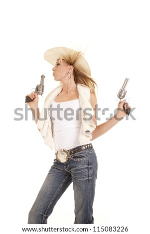 A cowgirl blowing on the tip of one of her two pistols with the wind blowing her hair - stock photo