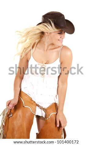 A cowgirl has both hands on her chaps and looking to the side. - stock photo