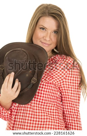 A cowgirl holding on to her hat with a small smile on her lips. - stock photo