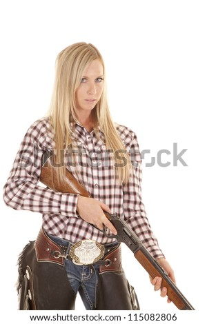 A cowgirl holding on to her rifle with  a serious expression on her face. - stock photo