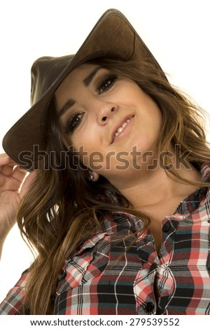A cowgirl in her plaid top looking with a smile. - stock photo