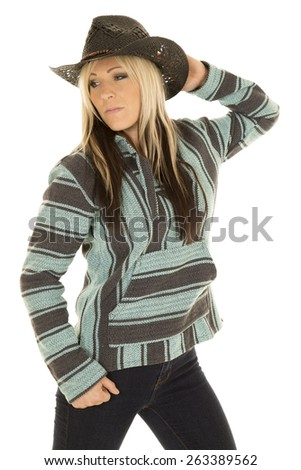 A cowgirl in her poncho, with her hand on her hat showing some attitude. - stock photo