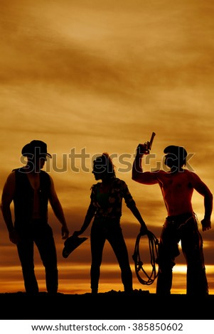 a cowgirl in the middle of two cowboys, in the outdoors. - stock photo