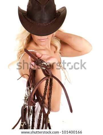 A cowgirl is standing holding a bridle and wearing a hat. - stock photo