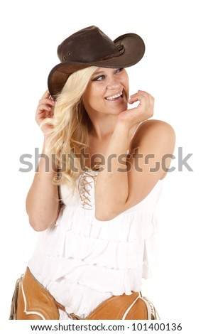 A cowgirl is very happy and wearing chaps and a hat. - stock photo