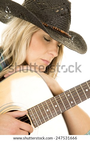 A cowgirl laying her head on the guitar with her eyes closed. - stock photo
