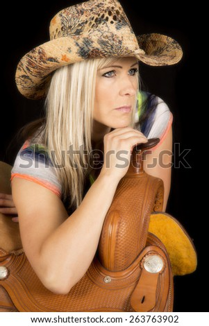 A cowgirl looking off to the side, leaning on her saddle. - stock photo