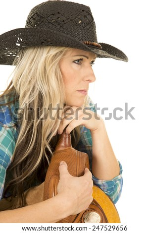 A cowgirl looking to the side in her plaid shirt wearing her black western hat, and laying on her saddle. - stock photo