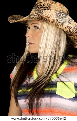A cowgirl looking to the side, wearing her cowgirl hat. - stock photo