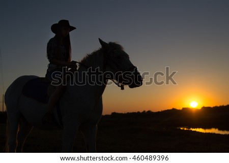 A cowgirl riding a horse in the middle of a grassy field on a ranch is silhouetted against the afternoon sun.