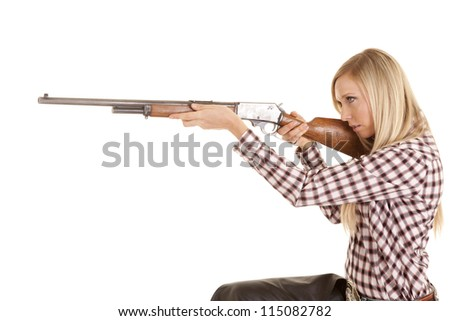 a cowgirl sitting down and aiming her rifle. - stock photo