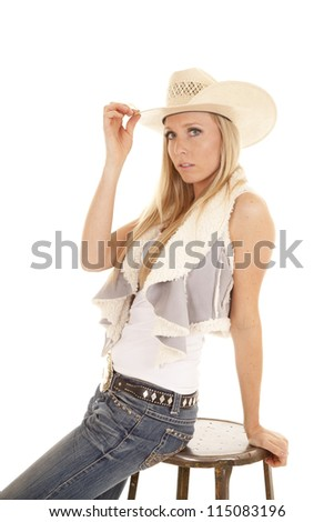 A cowgirl sitting on a stool with a serious expression on her face touching the brim of her hat. - stock photo