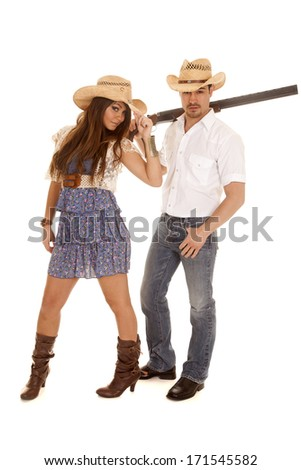 a cowgirl standing in front of her man while he is holding on to a gun. - stock photo