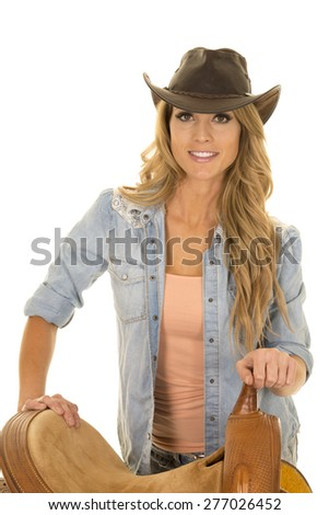 A cowgirl standing next to her saddle with a big smile on her lips. - stock photo