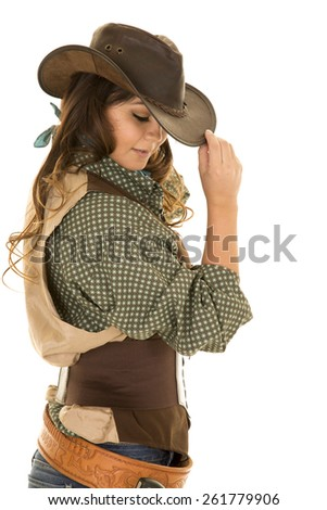 A cowgirl touching the brim of her hat looking down, with her holster on her waist.