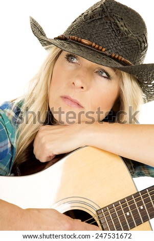 A cowgirl with a far away look, holding to the guitar up close. - stock photo