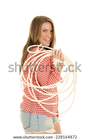 A cowgirl with a smile holding her rope over her shoulder. - stock photo