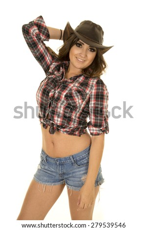 A cowgirl with a smile in her short shorts and plaid top. - stock photo