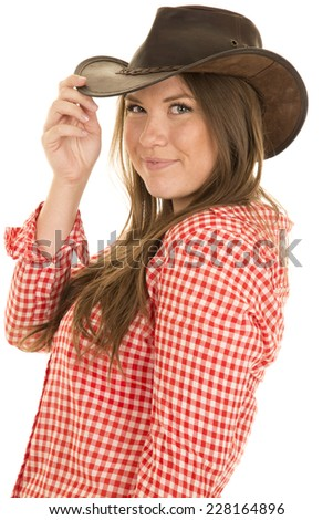 a cowgirl with a smile touching the brim of her hat. - stock photo
