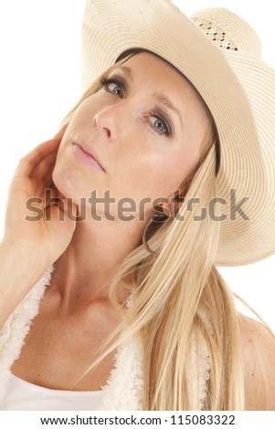 A cowgirl with her head bent to the side with a serious expression on her face. - stock photo