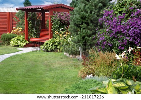 a cozy corner of the garden with a bench, lawn and flowering clematis - stock photo