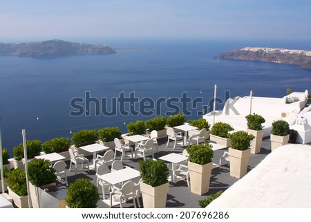A cozy terrace with chairs and a table. View to the caldera, Santorini, Greece