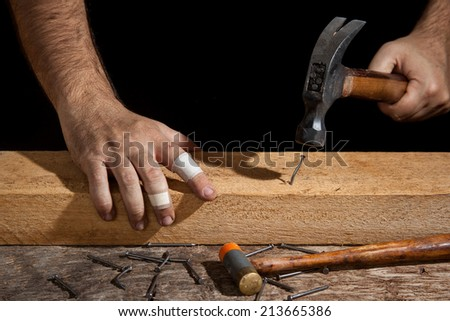 A craftsman hammering bent nail with difficulty