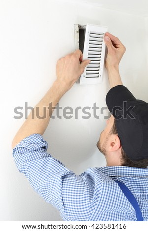 A Craftsmen changing a Ventilation filter 2 - stock photo