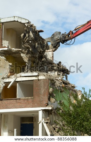 A crane is demolishing a block of flats - stock photo