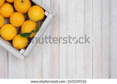 A crate of fresh picked lemons on a rustic white wood table in the upper left corner of the frame. Horizontal format with copy space. - stock photo