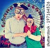 a crazy looking couple at a fair in front of the ferris wheel done with a retro vintage instagram filter  - stock photo