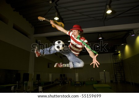 a crazy soccer fan flying high with a soccer ball and guitar imagination running wild. - stock photo