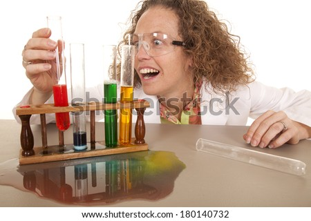 A crazy woman scientist with some test tubes full of colored liquid. - stock photo
