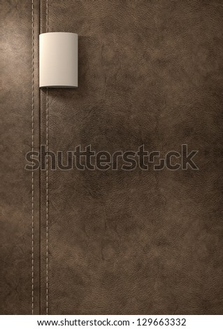 A cream woven clothing label sewn into seamed and stitched brown leather - stock photo