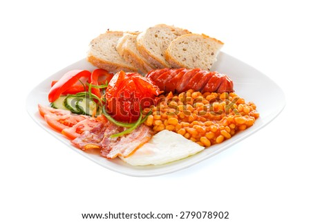 A creative arranged continental breakfast containing sausages, bean truck, bacon, fresh vegetables, fried eggs and bread. - stock photo