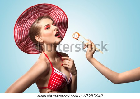 A creative vintage photo of a beautiful pin-up girl in bikini and hat being fed with sushi. - stock photo