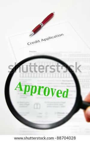 a credit application and magnifying glass with Approved text - stock photo