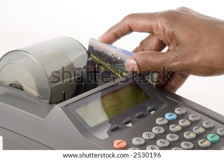A credit card is swiped in a credit card machine - stock photo