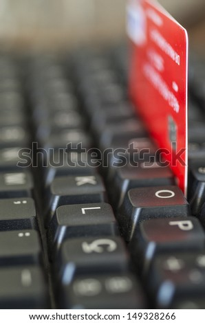 A credit card wedged into the keys of a keyboard - stock photo