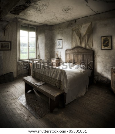 A creepy bedroom scenery, cracked walls and wooden floors along with a religious atmosphere. - stock photo
