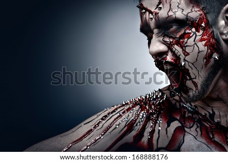 A creepy halloween concept of a screaming moor in pain with a piercing and bloody body art. - stock photo