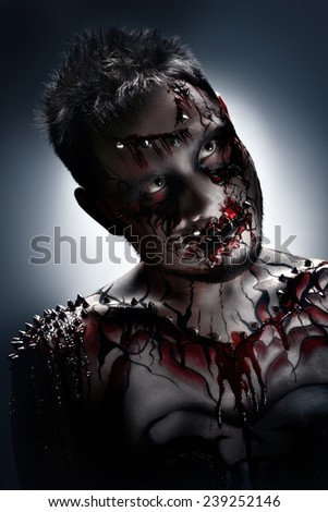 A creepy portrait of a pierced halloween moor with bloody body art. - stock photo