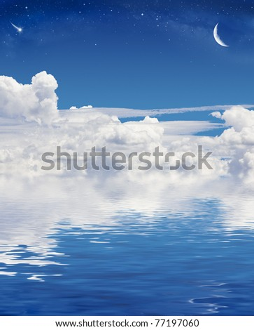 A crescent moon and shooting star above a sky of clouds reflected in a calm sea. - stock photo
