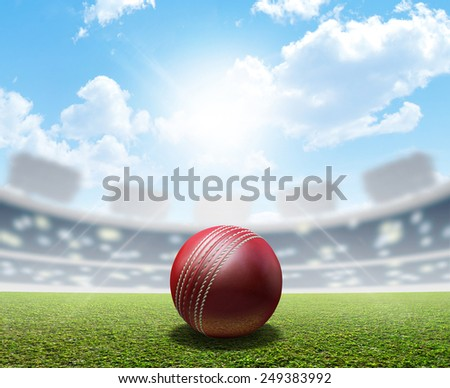 A cricket stadium with a red leather cricket ball on an unmarked green grass pitch in the daytime under a blue sky  - stock photo