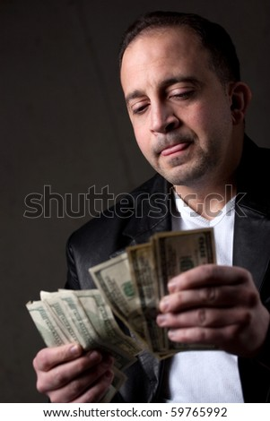 A crooked looking man counting a handful of one hundred dollar bills. Shallow depth of field with focus on the face. - stock photo