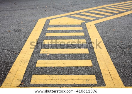 A crooked yellow zebra crossing on a asphalt road.
