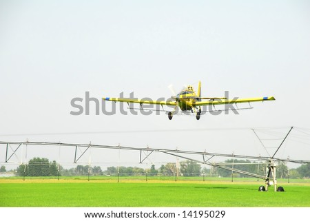 A crop duster or spray plane flies over a an irrigation system in a green grain field. - stock photo