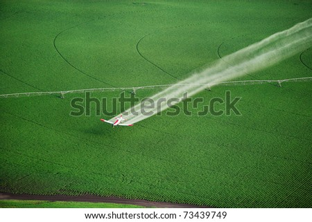 A crop duster working in a farm field - stock photo